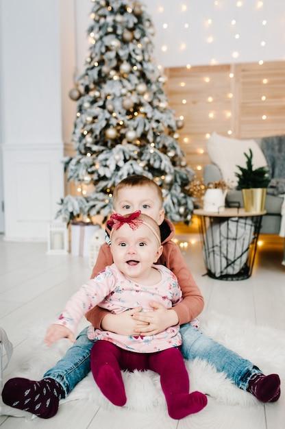 Kinder sitzen auf dem boden in der nähe von weihnachtsbaum. fröhliche weihnachten. weihnachten dekoriertes interieur. das konzept des familienwinterurlaubs. Premium Fotos