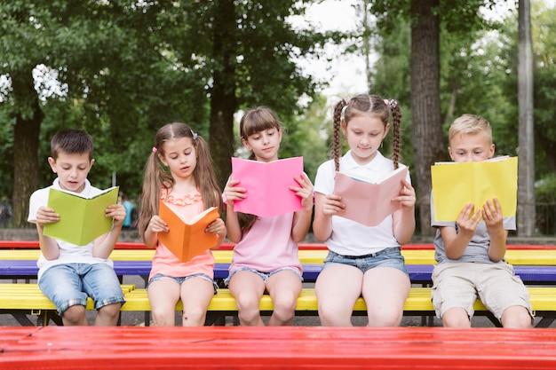 Kinder sitzen auf der bank und lesen Kostenlose Fotos