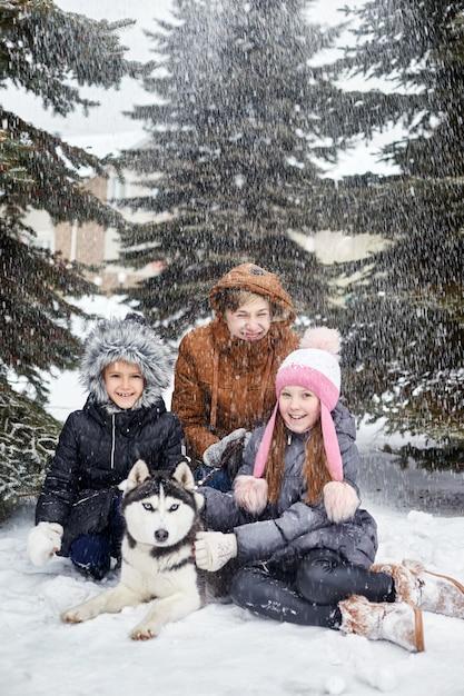 Kinder sitzen im schnee und streichelten hundeschlittenhund. kinder gehen raus und spielen im winter mit dem heiseren hund Premium Fotos