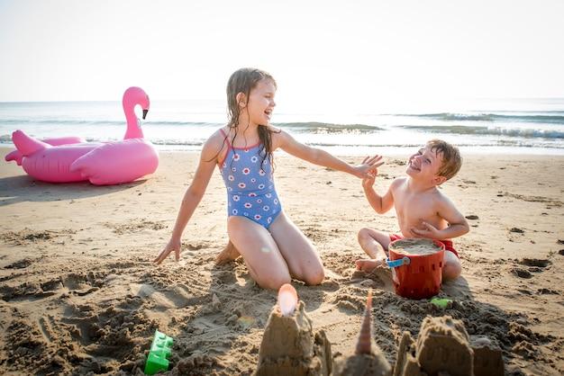 Kinder spielen am strand Premium Fotos
