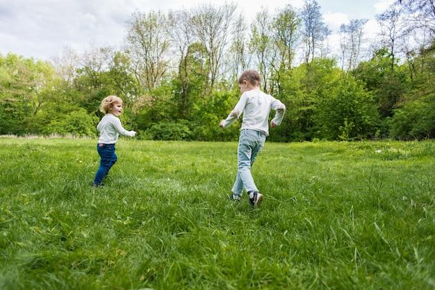 Kinder spielen auf dem grünen rasen im freien, laufen und haben spaß Premium Fotos