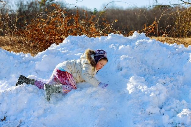 Kinder spielen außerhalb der wintersaison glückliches kind spielt im schnee in der nähe eines waldes Premium Fotos