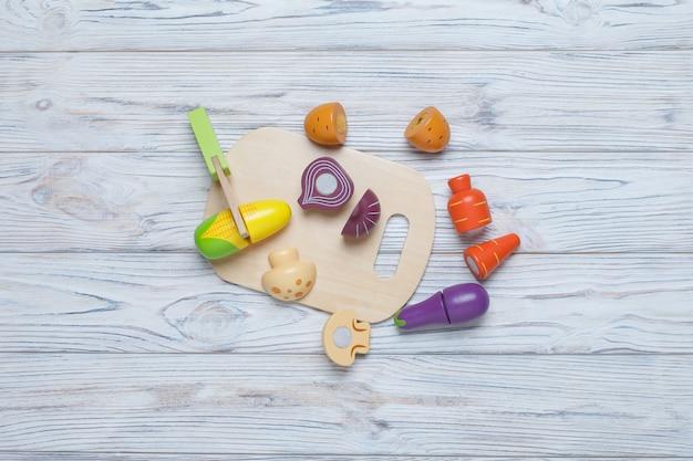 Kinder spielen holzgemüse. kinder entwickeln holzspiel. eine reihe von holzgemüse mit platz für text. plastikspielzeugküche für kinder. in scheiben geschnittenes spielzeuggemüse Premium Fotos