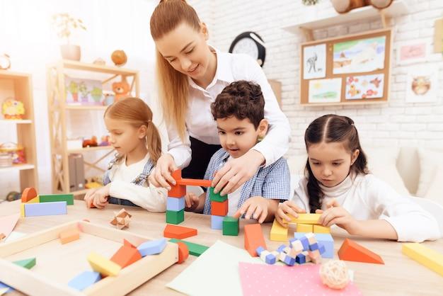 Kinder spielen mit holzwürfeln und lehrer hilft ihnen. Premium Fotos