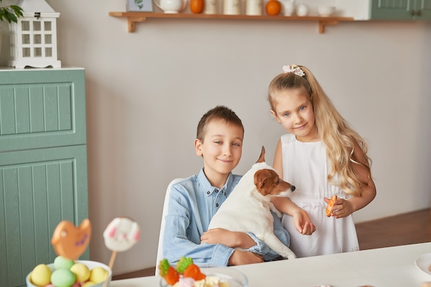 Kinder spielen mit ihrem hund auf einem mit ostern geschmückten tisch Premium Fotos