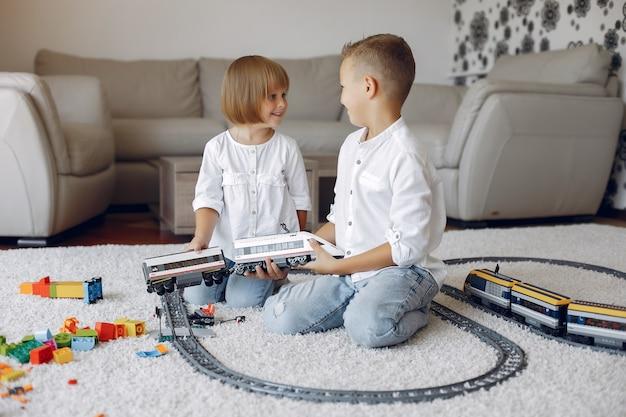 Kinder spielen mit lego und spielzeugeisenbahn in einem spielzimmer Kostenlose Fotos