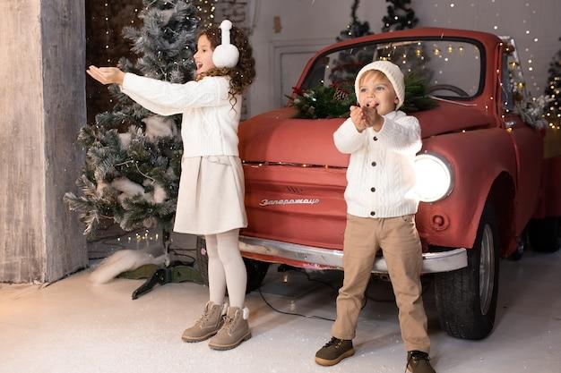 Kinder spielen mit schnee nahe rotem auto und weihnachtsbaum und lichtern Premium Fotos