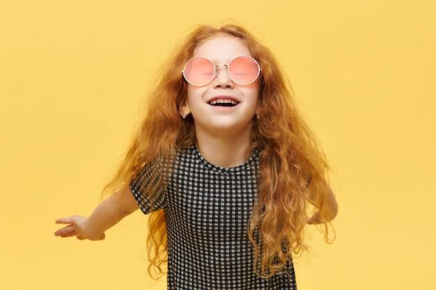 Kinder, stil und fshion konzept. sorgloses modisches kleines mädchen mit lockigem rotem haar, das glücklichen freudigen gesichtsausdruck hat, lacht, stilvolle rosa sonnenbrille trägt und arme hinter ihrem rücken hält Kostenlose Fotos
