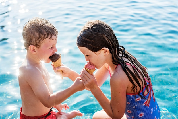 Kinder teilen eis am pool Premium Fotos
