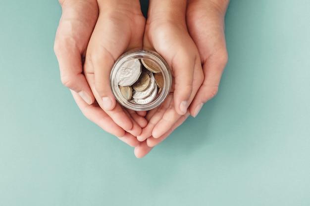 Kinder- und elternhände, die geldglas, spende, sparen, familienfinanzierungsplankonzept halten Premium Fotos
