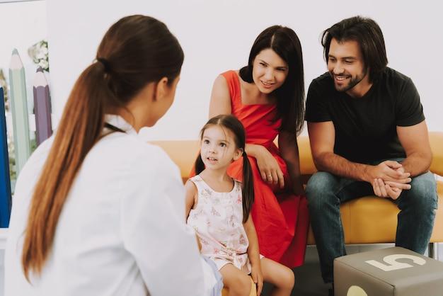 Kinderarzt spricht mit kleinem mädchen im büro Premium Fotos