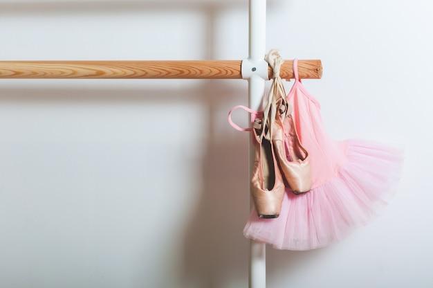 Kinderballett-kleid und ballett-schuhe, die an einen ballett-barre halten. tanz-konzept. Premium Fotos