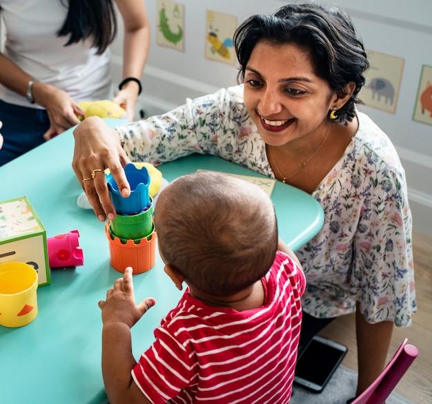 Kinderbausteine mit einem lehrer im kindergarten Premium Fotos
