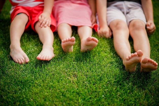 Kinderbeine auf dem rasen. nackte beine von kleinen mädchen sitzen auf der wiese. geringe tiefenschärfe, kinder sitzen auf dem rasen mit bloßen beinen Premium Fotos