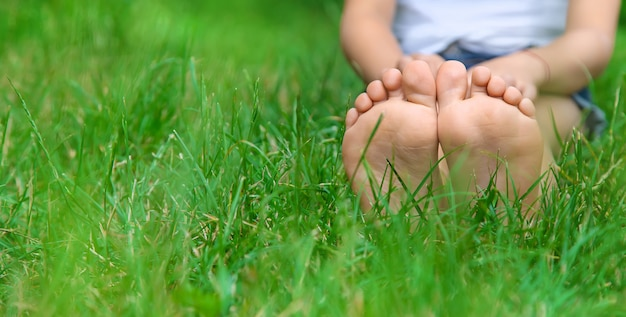 Kinderfüße auf dem grünen gras im park. Premium Fotos