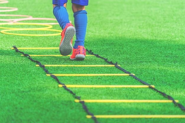 Kinderfüße mit fußballstiefeln ausbildend auf beweglichkeitsgeschwindigkeitsleiter im fußballtraining. Premium Fotos