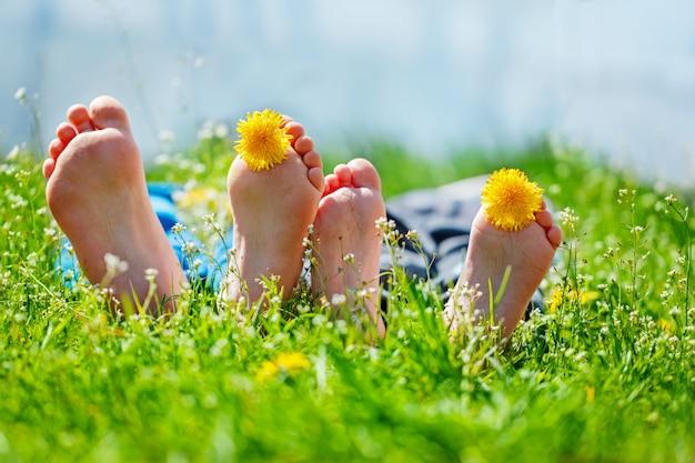Kinderfüße mit löwenzahnblumen, die auf grünem gras am sonnigen tag liegen. konzept glückliche kindheit. Premium Fotos