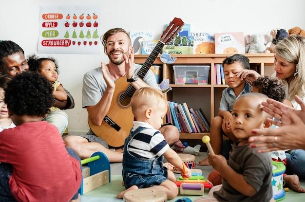 Kindergartenkinder, die mit musikinstrumenten im klassenzimmer spielen Premium Fotos