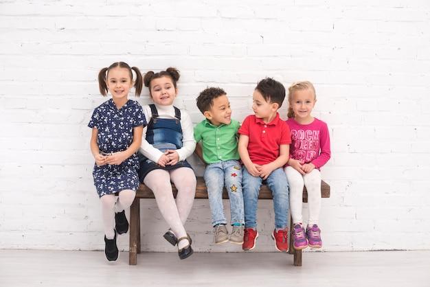 Kindergruppe saß auf einer bank Kostenlose Fotos