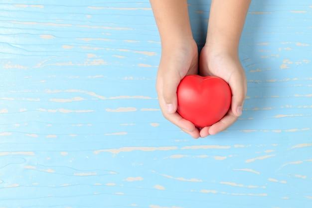 Kinderhände, die rotes herz auf purpleheart halten Premium Fotos