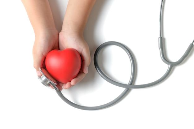 Kinderhände, die rotes herz mit dem stethoskop lokalisiert halten Premium Fotos