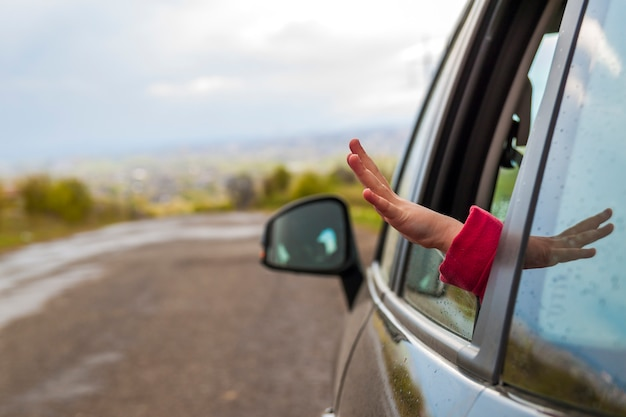 Kinderhände in einem autofenster während der reise zu den ferien Premium Fotos