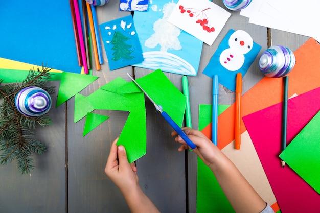Kinderhände machen handgemachtes weihnachtsspielzeug aus pappe. kinder diy. Premium Fotos