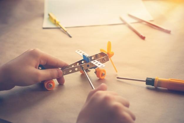 Kinderhände mit spielzeugeisenflugzeug. metallbauer mit schraubendreher. träume, spiele und erschaffe Premium Fotos