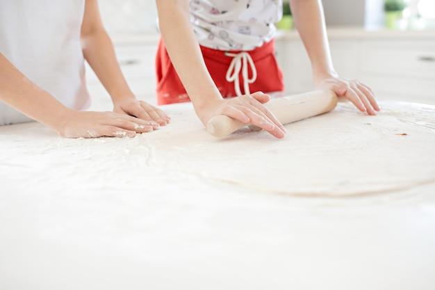Kinderhände rollen den pizzateig auf einem weißen tisch aus. gemeinsam spaß in der küche haben. von oben betrachten. Premium Fotos