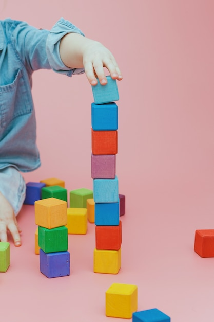 Kinderhand baut einen turm aus hölzernen farbigen würfeln. Premium Fotos