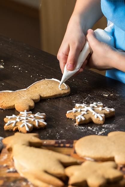 Kinderhand, die plätzchen mit zucker verziert. Premium Fotos