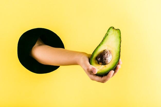 Kinderhand hält eine avocado aus einem schwarzen loch in einer gelben papierwand Premium Fotos