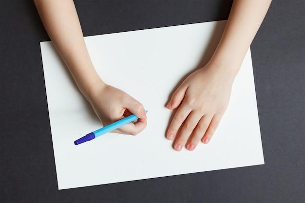 Kinderhand mit einem stift auf einem weißbuch Premium Fotos