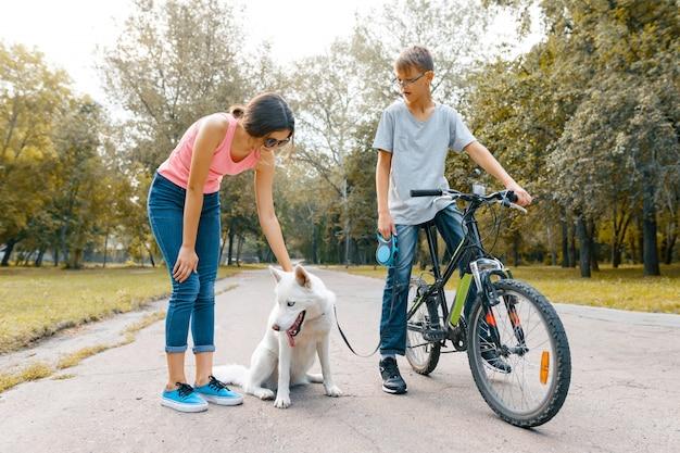 Kinderjugendliche auf der straße im park mit weißem hundeschlittenhund Premium Fotos