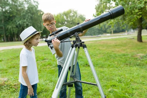 Kinderjugendliche im park, der durch ein teleskop schaut Premium Fotos