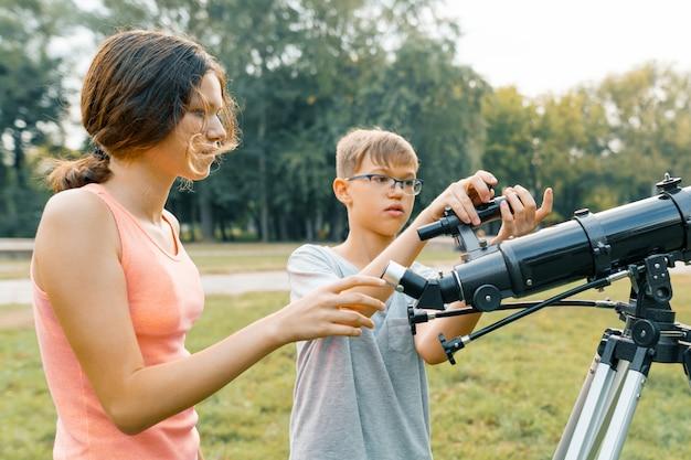Kinderjugendliche mit teleskop betrachten den himmel in der natur Premium Fotos