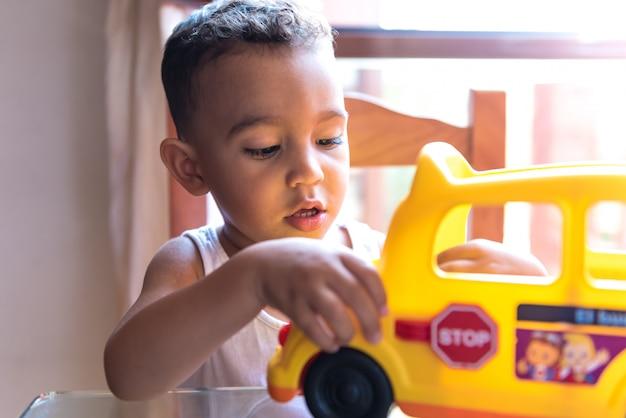 Kinderjunge, der zuhause mit einem schulbusspielzeug spielt. Premium Fotos