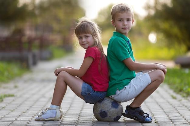 Kinderjunge und -mädchen, die auf fußball sitzen Premium Fotos