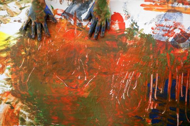 Kinderkünstlerhände, die multi farben malen Premium Fotos