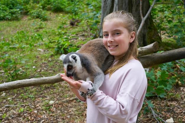 Kindermädchen, das spaß mit ring angebundenem lemurtier hat Premium Fotos