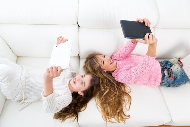 Kindermädchen, die spaß haben, mit liegendem sofa des tabletten-pc zu spielen Premium Fotos