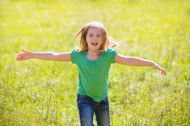 Kindermädchen glücklich, offene hände in grünem im freien laufen zu lassen Premium Fotos