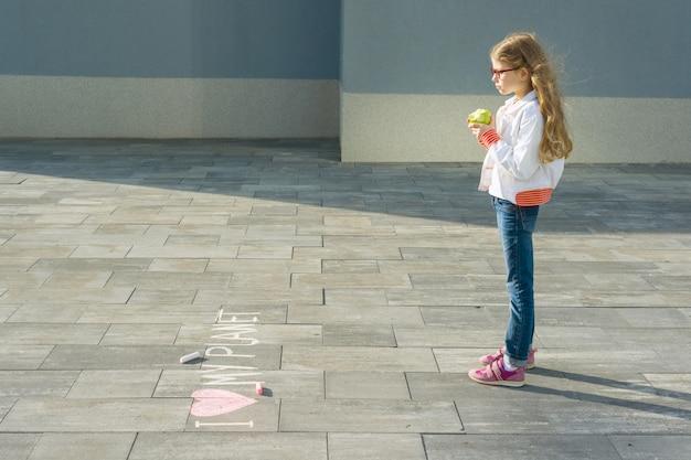 Kindermädchen schrieb auf den asphalt, den ich meinen planeten liebe Premium Fotos