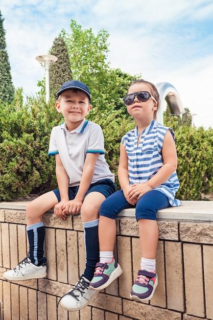 Kindermode-konzept. der jugendlich junge und das mädchen sitzen im park. Kostenlose Fotos