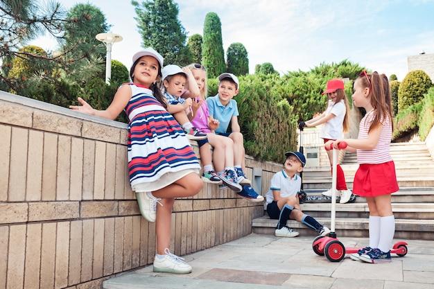 Kindermode-konzept. gruppe von jugendlich jungen und mädchen, die am park aufwerfen Kostenlose Fotos