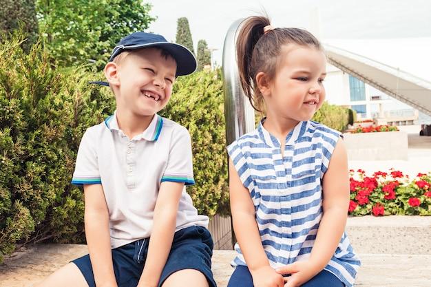 Kindermode-konzept. jugendlich junge und mädchen, die am park sitzen Kostenlose Fotos