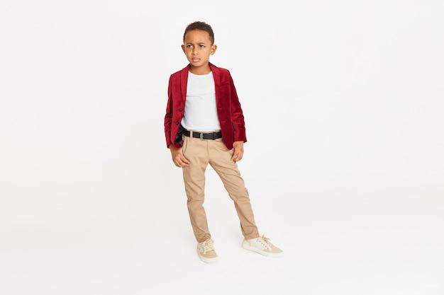 Kindermode, stil, schönheit und ethnische zugehörigkeit konzept. isolierte aufnahme in voller länge des selbstbewussten ernsthaften afroamerikanischen schuljungen, der gegen kopierraumhintergrund aufwirft Kostenlose Fotos
