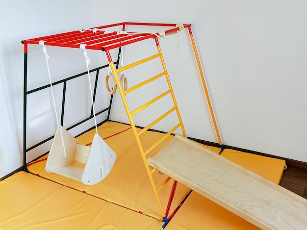 Kindersportkomplex für kleinkinder in der wohnung holzschaukel, klettergerüst, rutsche und turnringe. Premium Fotos