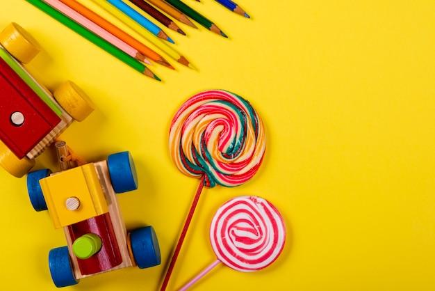 Kindertag. hölzerner zug, lutscher und farbbleistift auf gelbem hintergrund Premium Fotos