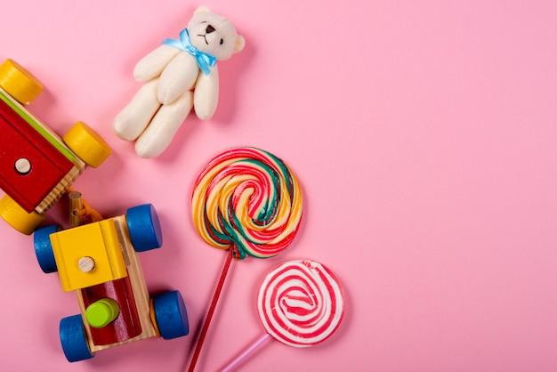 Kindertag. hölzerner zug, lutscher und teddybär über rosa hintergrund Premium Fotos